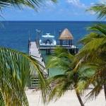 Mayordomos con Karisma frente a aguas azul turquesa en Cancún
